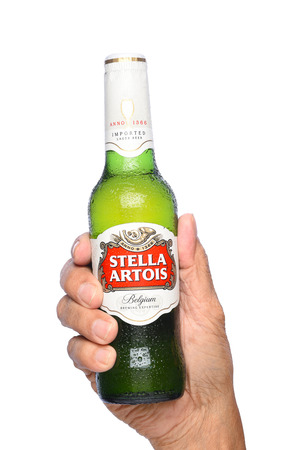 IRVINE, CALIFORNIA - APRIL 26, 2019: Closeup of a hand holding a bottle of Stella Artois Beer. Stella is brewed in Leuven, Belgium, and launched as a festive beer, named after the Christmas star. Editorial