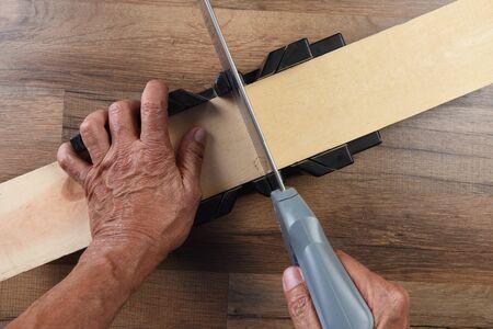 Nahaufnahme eines Holzarbeiters mit einer Gehrungslade und einer Handsäge, um ein Brett zu schneiden.