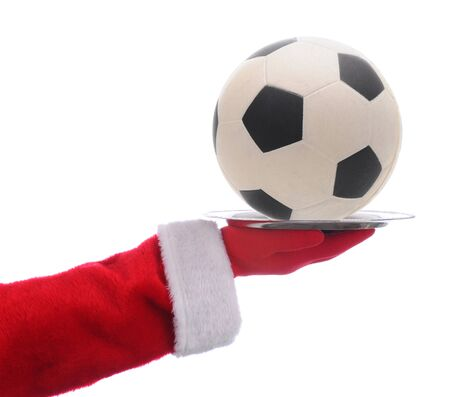 Santa Claus holding a serving tray with a Soccer Ball over a white background.
