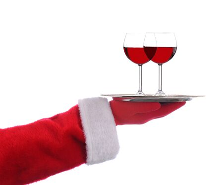 Santa Claus outstretched arm holding a silver serving tray with two glasses of red wine over a white background.