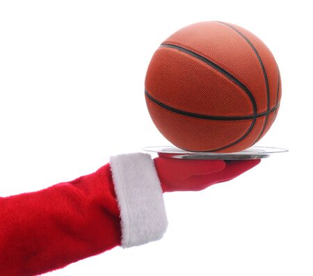 Santa Claus holding a serving tray with a basketball over a white background.