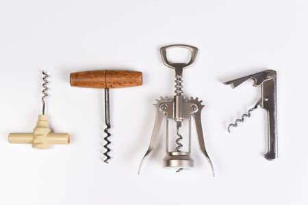 Assorted corkscrews on white. Four different styles of wine openers in a row.