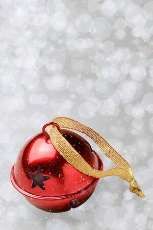 A single red jungle bell on a silver bokeh background with snow effect in vertical format with copy space. Stock Photo