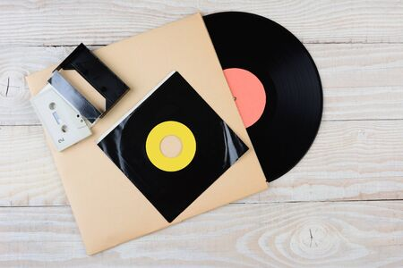High angle shot of retro style music formats. Items include: Vinyl LP, 45 rpm single, and a cassette tape. Horizontal format on a white wood surface.