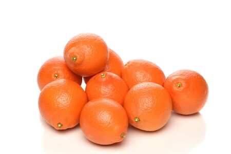 A pile of fresh picked Minneola Tangelos on white. The fruit is a cross between a Duncan grapefruit and a Dancy mandarin.