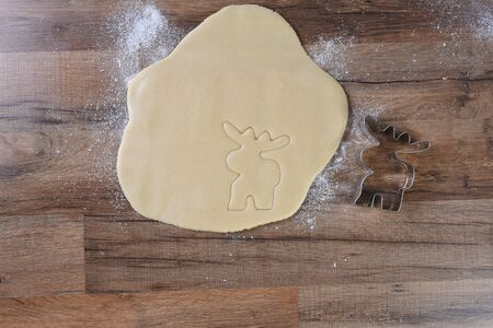 Moose shaped cookie cutter next to rolled out dough on a wood kitchen table.