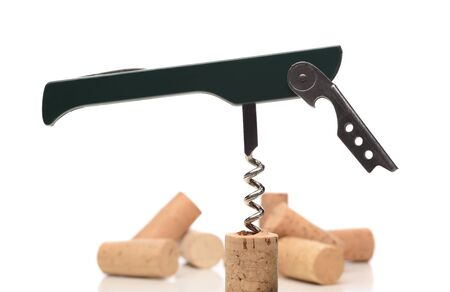 Closeup of a waiters corkscrew inserted into a cork isolated on white. a samll group of out of focus corks are in the background. Stock fotó