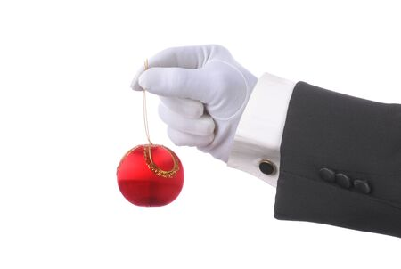 Man with formal gloved hand holding a red Christmas Ornament over white. Hand and arm only in horizontal format.