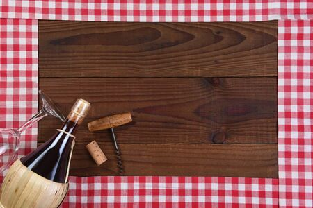 Red and white checked table runners forming a frame with a Basket bottle of Chianti Wine, a glass and corkscrew.