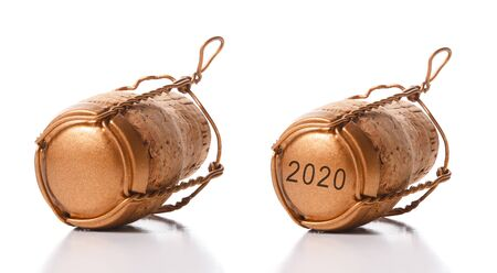 Closeup of two champagne corks with their cage on white with reflection. One cork has the date 2020.