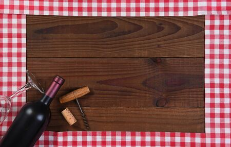 Red and white checked table runners forming a frame with a bottle of red wine, a glass and corkscrew.