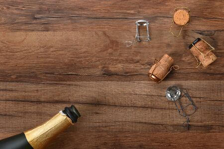High angle shot of an ope bottle of champagne with corks in opposite corners of the frame, on a wood table with copy space. Imagens