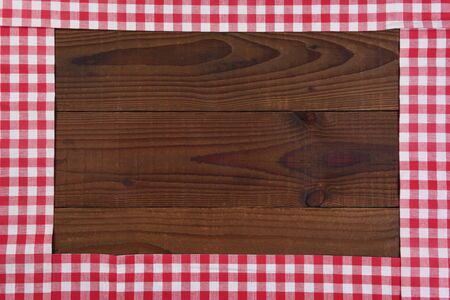 Red and white checked table runners forming a frame on a rustic dark wood table, with room for your copy.