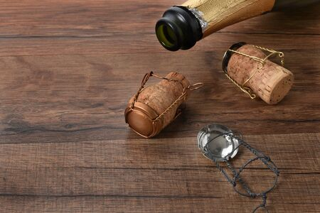High angle shot of an open bottle of champagne with corks on a wood table with copy space.