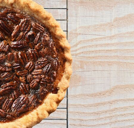 High angle view of a fresh baked holiday Pecan Pie on a cooling rack atop a rustic wood kitchen table. Only half the pie is shown leaving copy space.