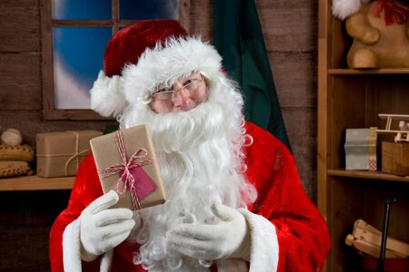 Santa Holding plain wrapped Christmas Present in his workshop Stock fotó