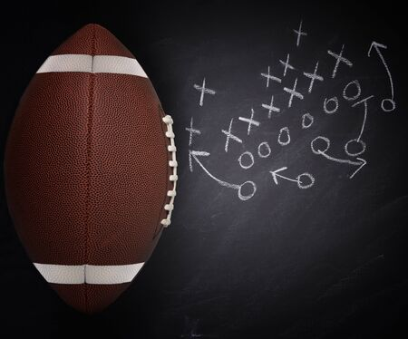 High angle flat lay of an American Collegiate Football and play diagram on a chalkboard.