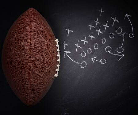 High angle flat lay of an American Pro Style Football and play diagram on a chalkboard. Banco de Imagens