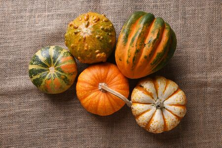 High angle shot of a group of autumn gourds, squash and pumpkins on burlap. Stock fotó