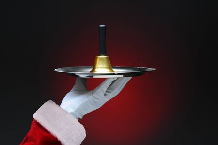 Closeup of Santa Claus hand holding a bell on a silver tray. Horizontal format on a light to dark red background. Archivio Fotografico - 136380165