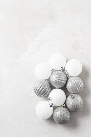 A group of silver and white Christmas Tree Ornaments on a light gray surface. Vertical with copy space. Archivio Fotografico - 136726109