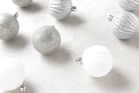 Christmas Tree Ornaments closeup with shallow depth of field. White and silver balls on a light gray table top. Archivio Fotografico - 136726113