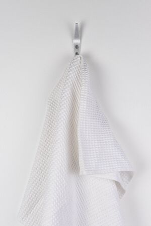 A white bath towel hanging from a hook on the white wall of a bathroom.  Stock Photo