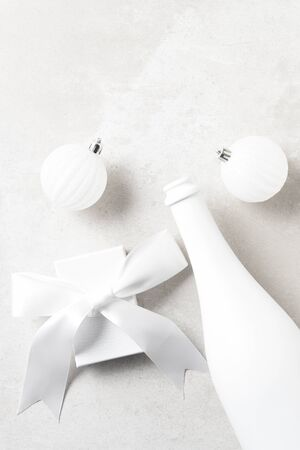 White Champagne bottle with white presents and Christmas Ornaments on a light gray table top. Flay lay with copy space. Archivio Fotografico - 136726120