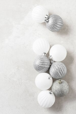 Silver and white Christmas Tree Balls on a light mottled gray surface. Vertical with copy space. Archivio Fotografico - 136726123