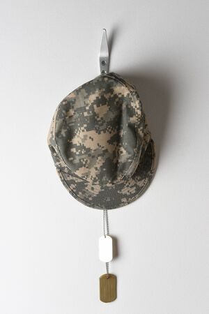 A set of military dog tags and field cap hanging from a hook on a blank wall. Stock Photo