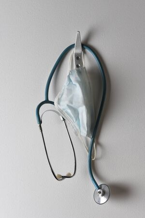 Closeup of a stethoscope and surgical mask hanging from a hook on a wall.