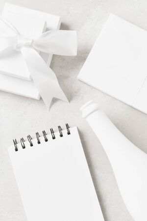 White flat lay still life with Gift Box, Champagne Bottle, a note pad and envelopes. Archivio Fotografico - 136726125