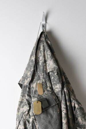 A set of military dog tags and camouflage field jacket hanging from a hook on a blank wall.