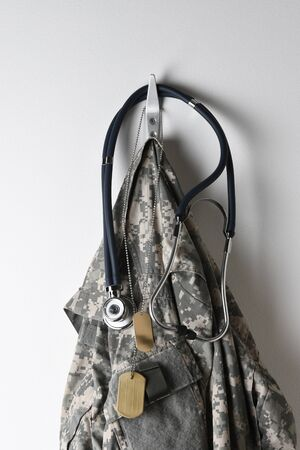 Military Healthcare Concept: A set of dog tags, Stethoscope and camouflage field jacket hanging from a hook on a blank wall. Stock Photo