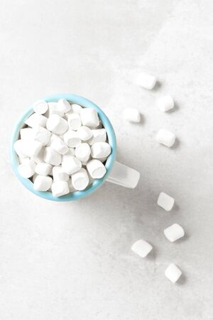 A white mug with blue rim filled with mini white marshmallows on a light gray tile surface. Archivio Fotografico - 136726130