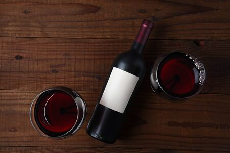 Wine Bottle with a blank label laying on its side and two full wine glasses on rustic wood table . Horizontal high angle shot with copy space.