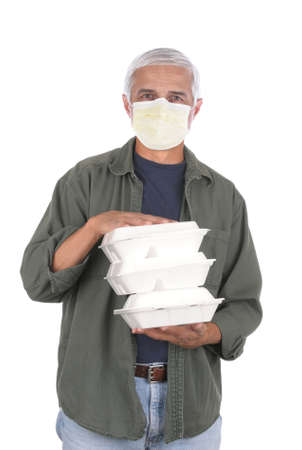 Food delivery man wearing covid-19 protective mask carrying three take-out food containers. Isolated on white. Stockfoto