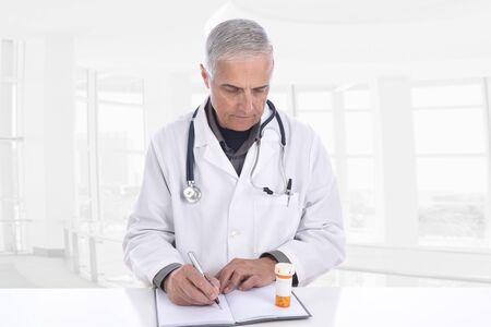 Doctor in a modern clinic setting taking notes as he looks at a prescription bottle.