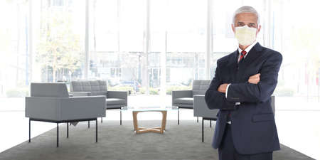 Businessman standing in empty office without customers or employees wearing his COVID-19 mask practicing social distancing. Wide format with copy space,