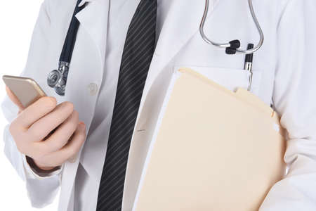 Closeup of a doctor holding his cell phone in one hand and file folders under his other arm. Man is unrecognizable. Stockfoto