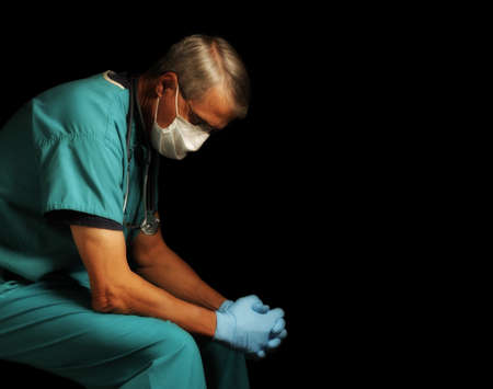 Exhausted Middle Aged doctor in scrubs, gloves and mask sitting with head down amid the Covid-19 crisis, profile portrait against black.