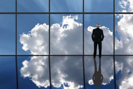 Businessman Standing in front of a large bank of windows with clouds and sun rays and reflection in the floor. Horizontal with copy space