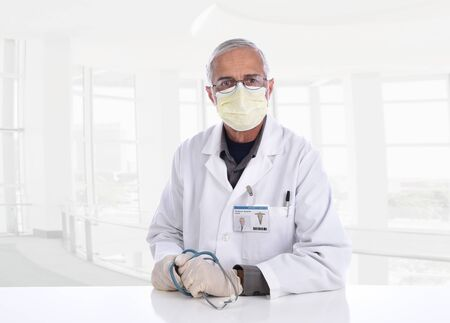 Medical Professional wearing a surgical mask, gloves and holding a stethoscope in a modern office setting. ID Badge is computer generated.