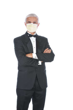 Mature Adult Male Wearing a Tuxedo and a Covid-19 protective mask with arms folded in front of body isolated on white