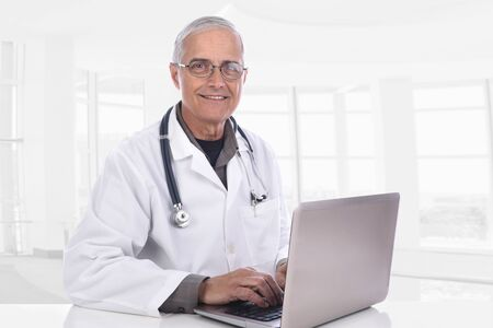 Smiling middle aged doctor Sitting at his desk using a computer in a modere medical facility. Banco de Imagens