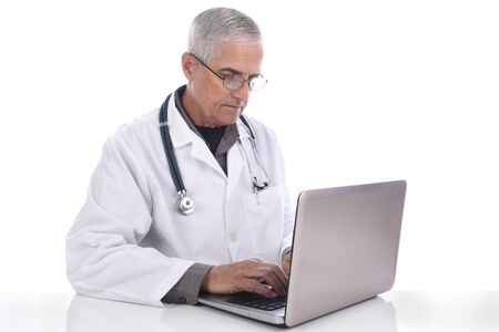 Portrait of a mature caucasian doctor at his desk with his laptop computer. Isolated on white.