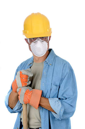 Construction worker wearing hard had and protective mask holding onto the handle of his shovel. Isolated over white in vertical format. Stockfoto