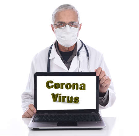 Coronavirus in large letters on a laptop computer screen. A Medical professional in surgical mask and lab coat is behind the computer. Stockfoto