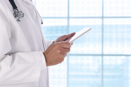 Closeup of a medical professional holding a tablet computer while standing in front of a large window in a modern medical facility.
