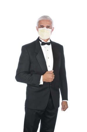 Mature Adult Male Wearing Tuxedo and Covid-19 protective mask, holding lapel and one hand at side, isolated on white.